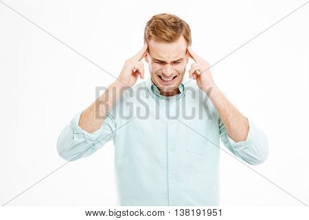 Stressful depressed blond man touching his temples and having headache over white background