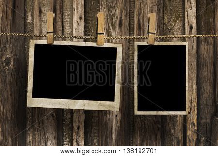 Aged photo frames on a rope with clothespins on wood background
