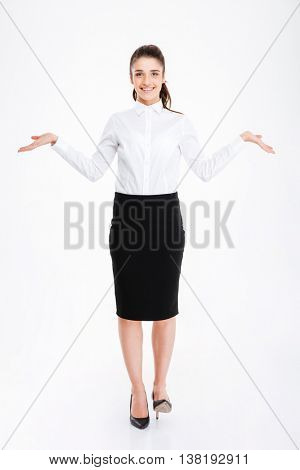 Happy young woman in formalwear holding copy space in both hands while standing isolated on white