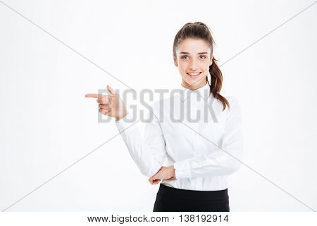 Portrait of a smiling young businesswoman pointing finger away over white background and looking at camera