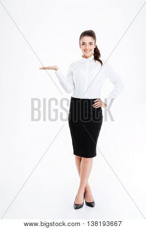 Full length portrait of a young beautiful businesswoman holding copy space isolated on the white background