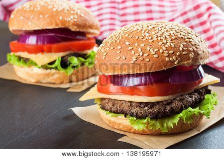 Two homemade cheeseburgers with beef patties and fresh salad on seasame buns, served on black slate board.