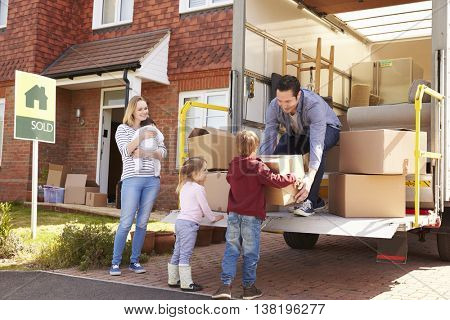 Family Unpacking Moving In Boxes From Removal Truck