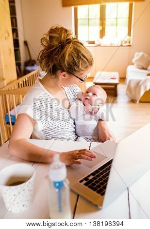 Close up of beautiful mother holding her baby son in the arms, working on laptop, milk in the bottle and coffee cup laid on table