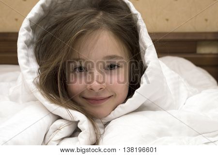 portrait of posing Caucasian brunette young girl of 7 - 8 years old laying in bed covered with white blanket over her head