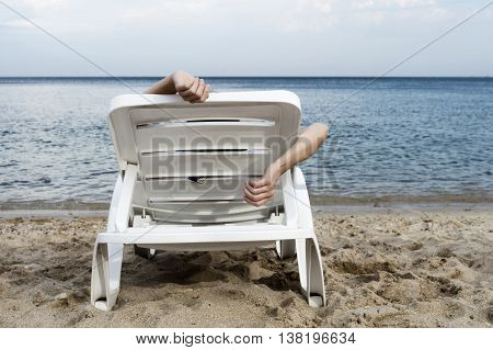 back view of woman lying on white plastic sun lounger with only arms visible. Sun lounger stands on sand with Sea and sky in background