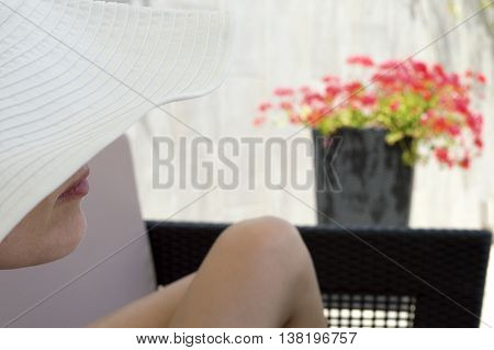 woman in white hat lying on lounge with legs spread out. Woman face partially covered with hat mouth and chin visible. Red flower in background