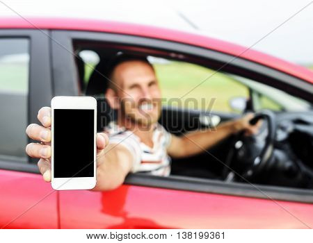 Man in car showing smart phone display smiling happy. Focus on mobile phone.