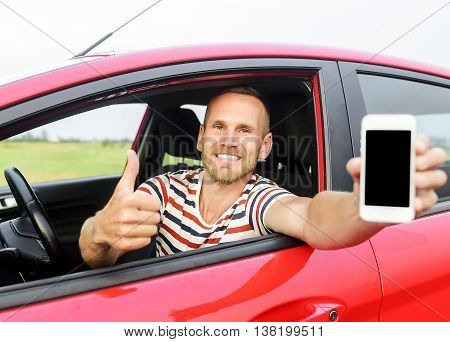 Man in car showing smart phone display and showing thumb up. Focus on model.