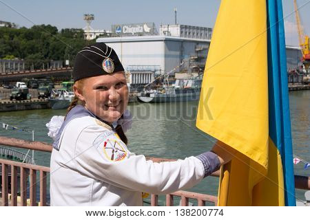 Odesa, Ukraine - July 03, 2016: red-haired girl with a flag of Ukraine in the navy uniform during celebration of Navy Day in Odessa