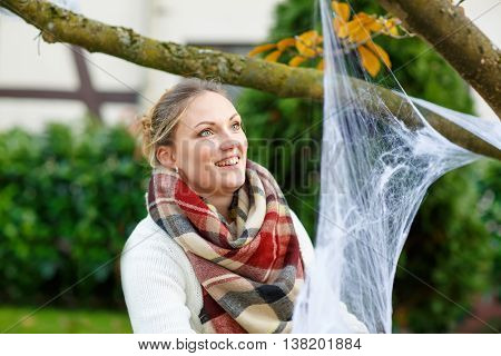 Young woman decorating home garden for halloween with spider web. Family celebrating holiday.