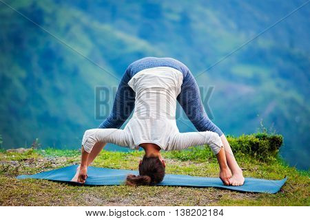 Yoga exercise outdoors -  woman doing Ashtanga Vinyasa Yoga asana Prasarita padottanasana  D - wide legged forward bend pose outdoors