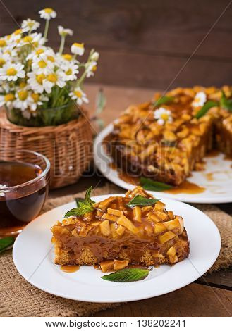 Apple Pie With Caramel Sauce On A Wooden Background