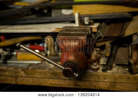 Old red metal vice in garage with tools