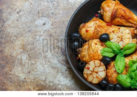 Grilled chicken legs with garlic basil olives and spices in a cast iron skillet.Top view. Copy space