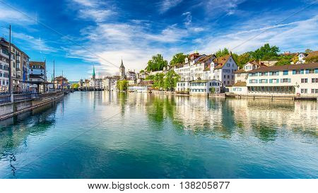 Beautiful view of the historic city center of Zurich with famous Fraumunster Church and swans on river Limmat on a sunny day with blue sky Canton of Zurich Switzerland