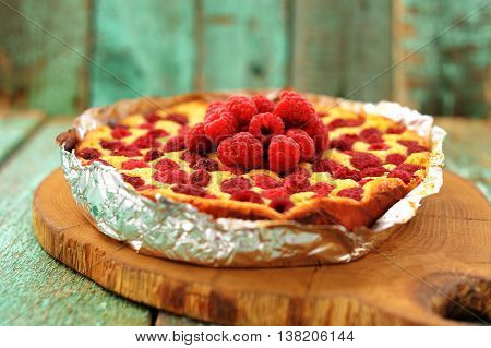 Homemade yummy quark pie with raspberries baked in foil selective focus closeup