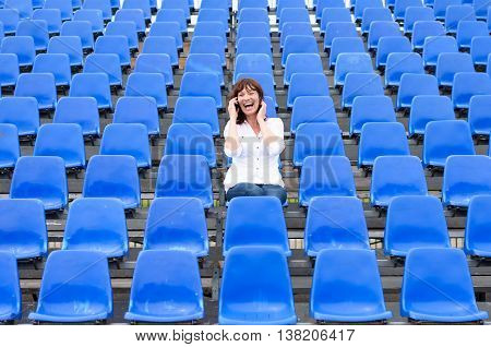 Lone middle-aged woman in a stadium sitting in the center of rows of empty blue seating chatting on her mobile phone and laughing happily