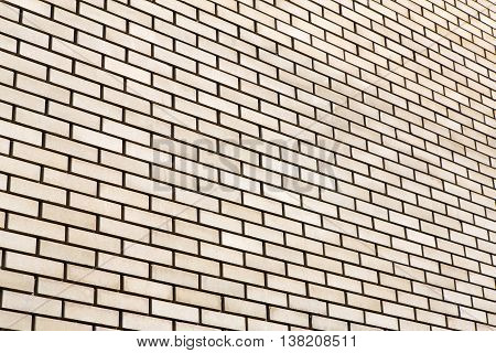 Beige brick wall background. Modern wall with smooth decorative false bricks texture. Brickwall stucco surface