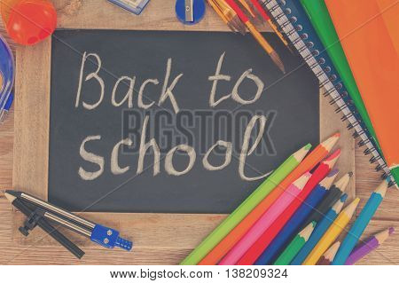 black chalk board with back to school and colorful school supplies, retro toned