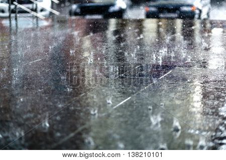 Heavy rain drops on asphalt with parked cars on background.