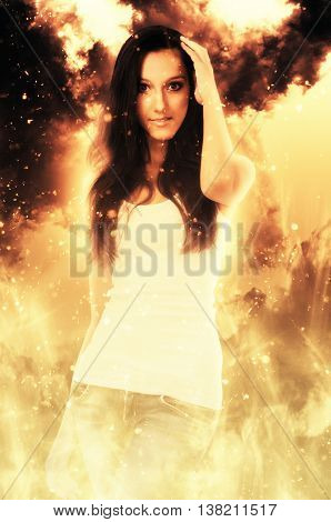 Beautiful grinning woman in white shirt holding hand near top of head while surrounded by flames