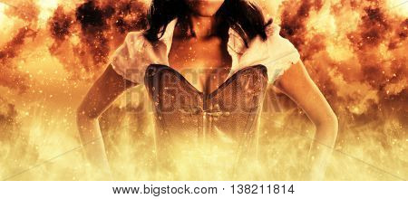 Sexy woman in a bustier engulfed in burning orange flames in a conceptual close up view of her upper torso standing with her hands on her hips