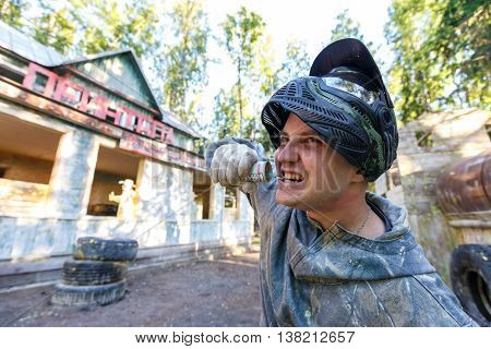 Paintball player pulling the pin of smoke grenade by his teeth