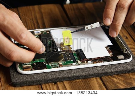Hands remove gsm sim card from nest on motherboard in electronic device that was broken