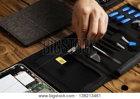 Hand holds tweezers with gsm sim card above tool bag in fixing service lab