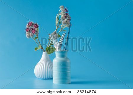 burdock wild blooming plant and forks on blue