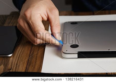 Pro uses plastic opener tool to open case of broken computer laptop to fix it