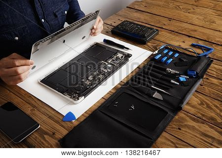 Service man opens backside topcase cover of computer laptop before repairing, cleaning and fixing it with his professional tools from toolkit box near on wooden table