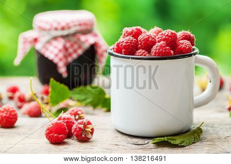 White Mug Of Raspberries And Jar Of Berry Jam On Background Outdoors