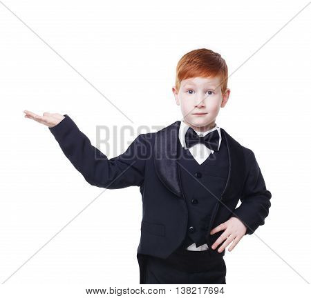 Little cute funny redhead boy in tailcoat tuxedo show something pointing at nowhere. Portrait of well-dressed child in bow tie isolated on white background