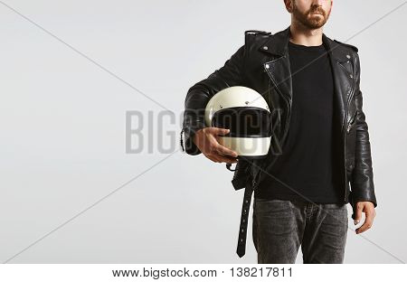 Brutal attractive bearded guy in tailored motorcycle leather jacket and classic helmet in hand poses in black blank t-shirt from premium thin cotton, isolated on white mockup