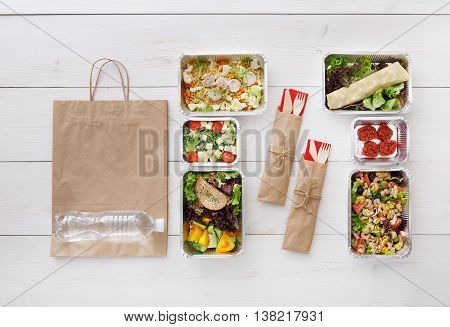 Healthy food delivery. Take away of natural organic low carb diet. Fitness nutrition in foil boxes, water bottle, cutlery and brown paper package. Top view, flat lay at white wood