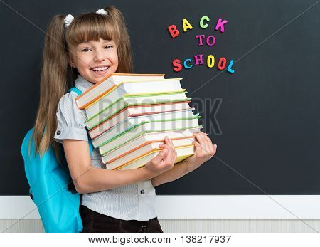 Back to school concept. Cute pupil with books at the black chalkboard in classroom.