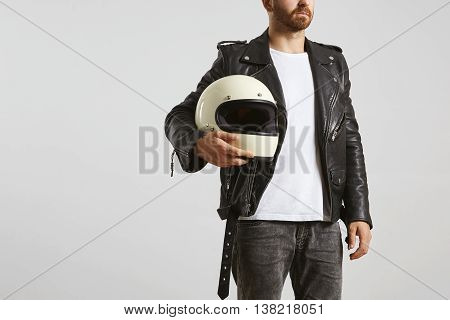 Brutal attractive bearded man in black geniune leather motorcycle jacket poses in white blank t-shirt from premium thin cotton, with biker helmet in his hand, isolated on white mockup