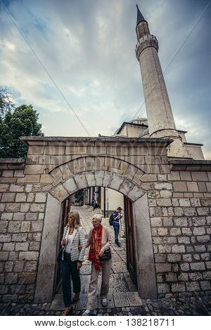 Sarajevo Bosnia and Herzegovina - August 23 2015. Two women goas out of the 16th century Ottoman style Gazi Husrev-beg Mosque located at Bascarsija area in Sarajevo
