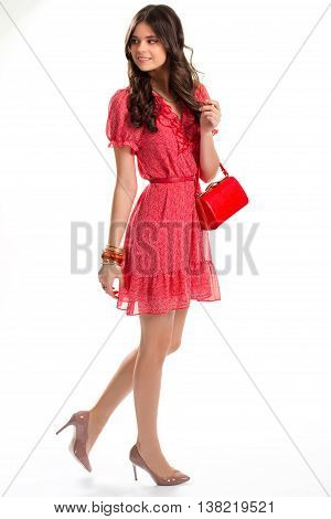 Woman in red dress. Girl with small purse. New accessories and heel shoes. Cute model is smiling.