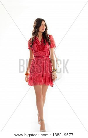 Girl in short summer dress. Casual dress of red color. Bead necklace and stylish bracelets. Attractive female model.