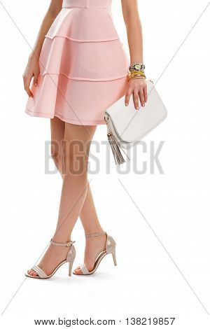 Lady in salmon dress. Beige heel shoes and handbag. Evening outfit with accessories. Stylish look for young girls.