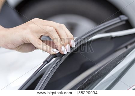 The wipers on the glass car regulates the hand of the girl.
