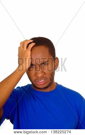 Headshot stressed man wearing strong blue colored t-shirt using hands touching his own head frustrated, white studio background.