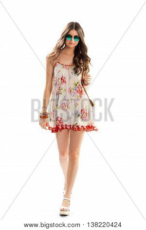Woman in dress is walking. Short floral dress and sunglasses. Small necklace with pendant. Young model wears summer outfit.