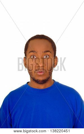 Headshot handsome man wearing strong blue colored t-shirt staring with empty facial expression into camera, white studio background.