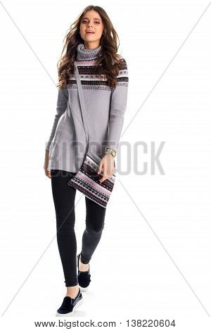 Girl in sweater is walking. Gray sweatshirt with print. Stylish slip ons and bag. Model wears casual autumn outfit.