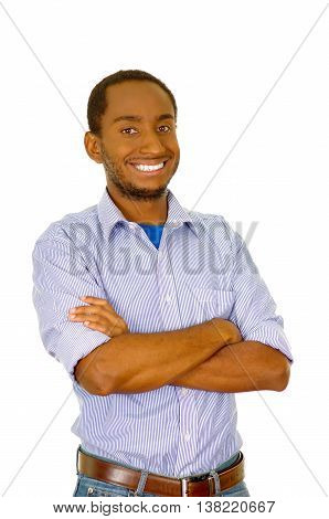 Handsome man wearing jeans and light blue shirt standing in front of camera smiling with arms crossed, white studio background.