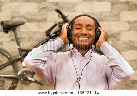 Man wearing white red business shirt sitting down, headphones on head, enjoying music with eyes closed while smiling happily, bicycle standing behind leaning against grey brick wall.